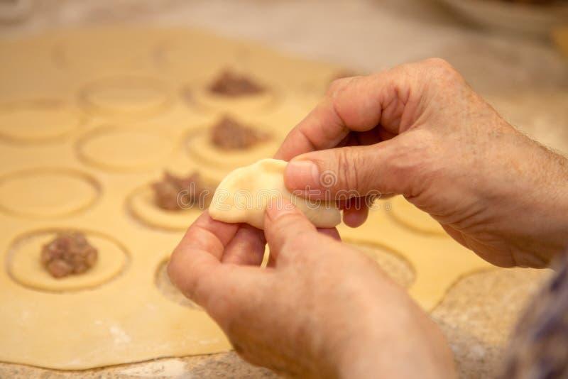 Les mains de la femme agée blanche rendent des boulettes en gros plan photos libres de droits