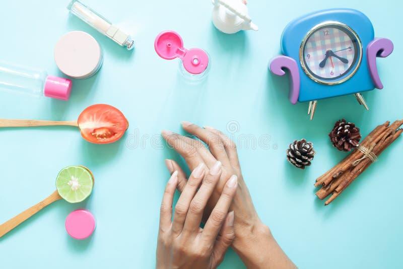 Les mains de la femme appliquant la lotion sur la peau Conteneurs cosmétiques et ingrédient naturel sur le fond en pastel images stock