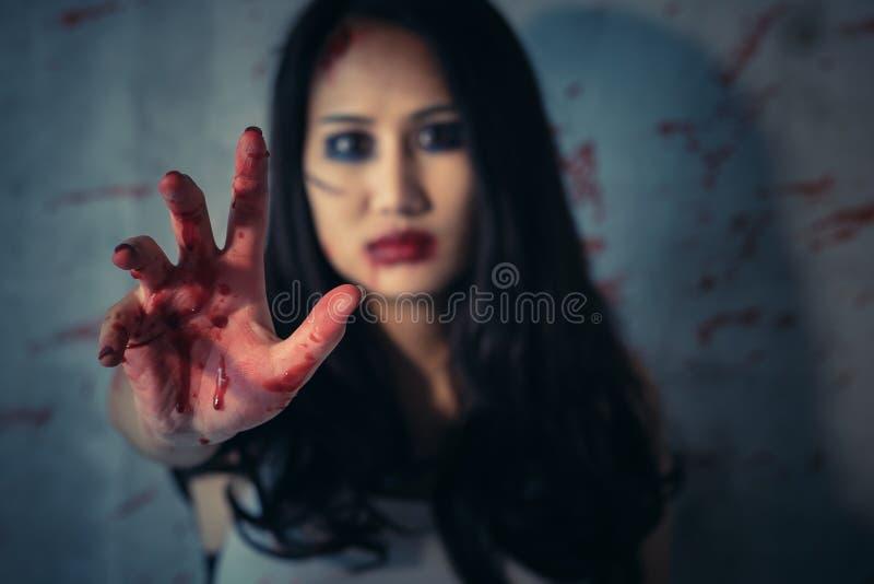 Les mains de la femme asiatique sont rouges ensanglanté à l'arrière-plan foncé, au concept du meurtre et au crime images stock