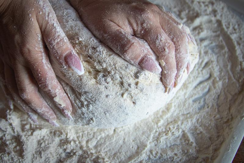 Les mains de la femme avec des ongles manucurés fonctionnent avec la pâte dans la cuisine photo libre de droits