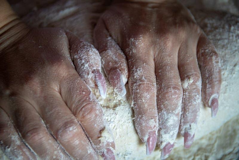 Les mains de la femme avec des ongles manucurés fonctionnent avec la pâte dans la cuisine images libres de droits