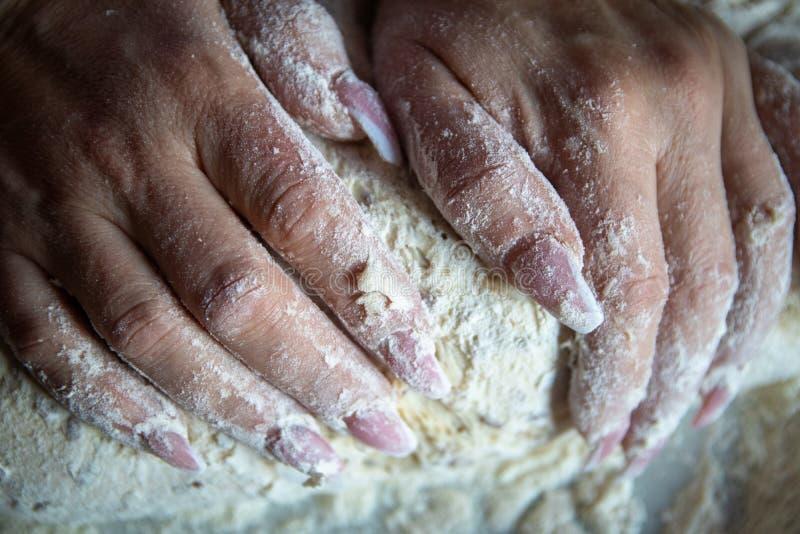 Les mains de la femme avec des ongles manucurés fonctionnent avec la pâte dans la cuisine photos stock