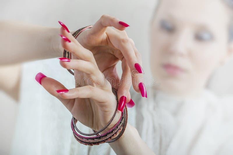 Les mains de la femme avec les clous et les bracelets rouges photo stock