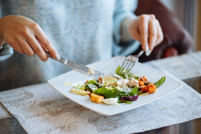 Les mains de la femme avec de la salade de César sur la table photo libre de droits