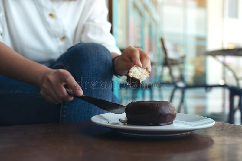 Les mains de la femme coupant un morceau de beignet de chocolat pour manger par le couteau et la fourchette dans un plat blanc image libre de droits