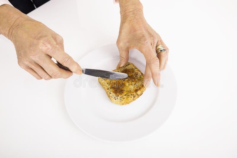 Les mains de la femme d'affaires répandant le beurre sur le pain photo libre de droits