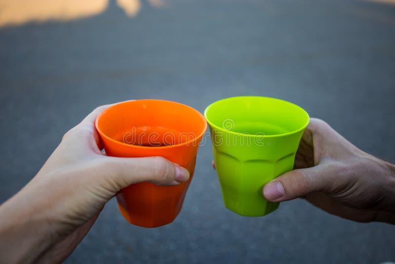 Les mains de la femme et des hommes jugeant la tasse chaude de thé extérieure au coucher du soleil images stock