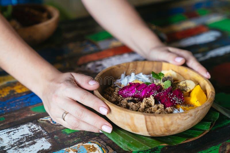Les mains de la femme jugeant le bol de smoothie fait avec la mangue, la banane, la granola, la noix de coco râpée, le fruit du d image libre de droits