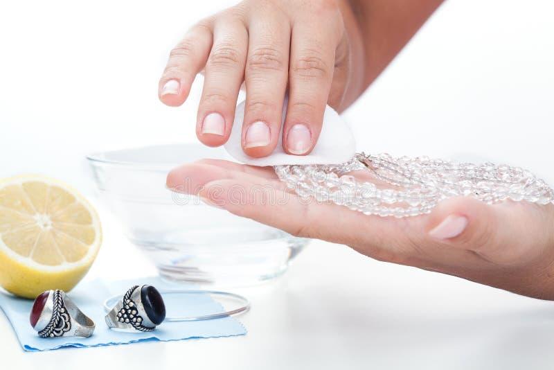 Les mains de la femme nettoyant des bijoux avec un citron photos libres de droits