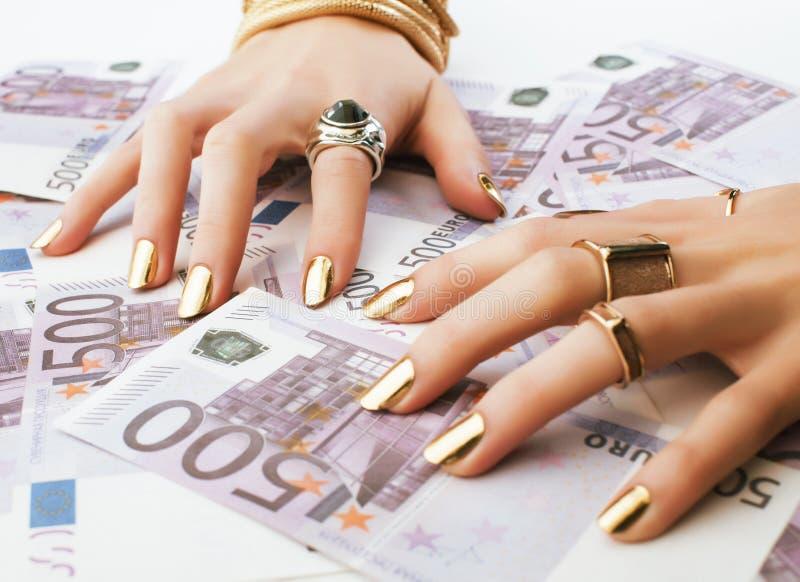 Les mains de la femme riche avec la manucure d'or et beaucoup d'anneaux de bijoux sur des euros d'argent liquide se ferment  photographie stock libre de droits