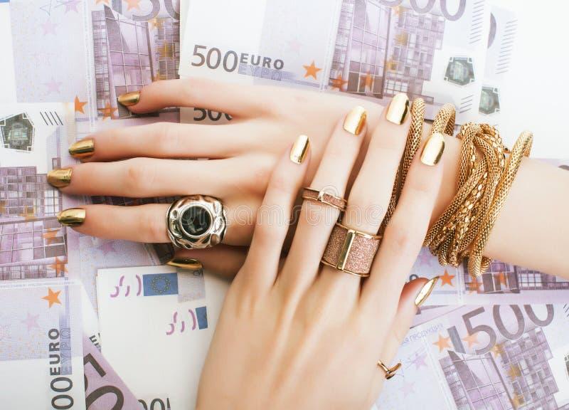 Les mains de la femme riche avec la manucure d'or et beaucoup d'anneaux de bijoux sur des euros d'argent liquide se ferment  images stock