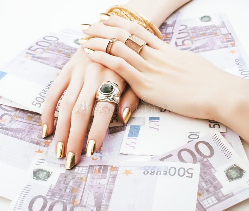 Les mains de la femme riche avec la manucure d'or et beaucoup d'anneaux de bijoux sur des euros d'argent liquide se ferment  photos libres de droits