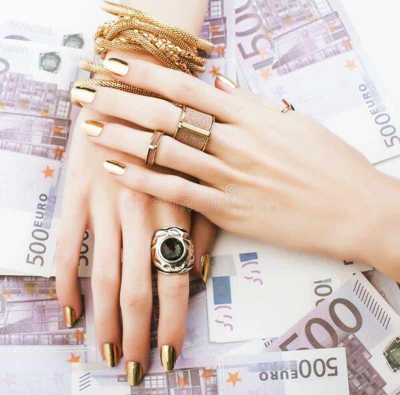 Les mains de la femme riche avec la manucure d'or et beaucoup d'anneaux de bijoux sur des euros d'argent liquide se ferment  image libre de droits