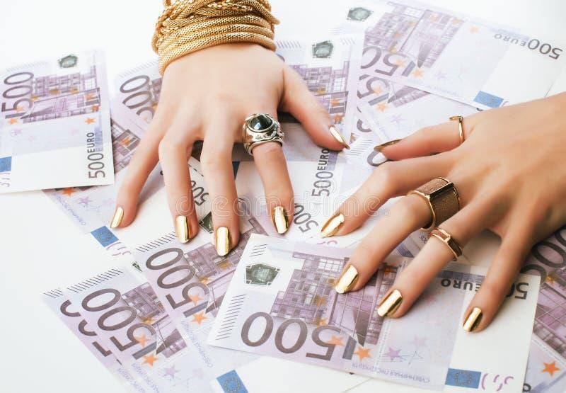 Les mains de la femme riche avec la manucure d'or et beaucoup d'anneaux de bijoux sur des euros d'argent liquide se ferment  photo libre de droits