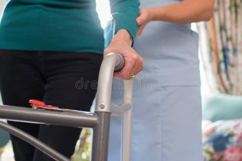 Les mains de la femme supérieure sur le cadre de marche avec le travailleur de soin dans Backgro image libre de droits
