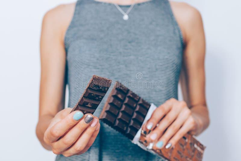 Les mains de la femme tenant la barre de chocolat et la tranche foncées de elle photos stock