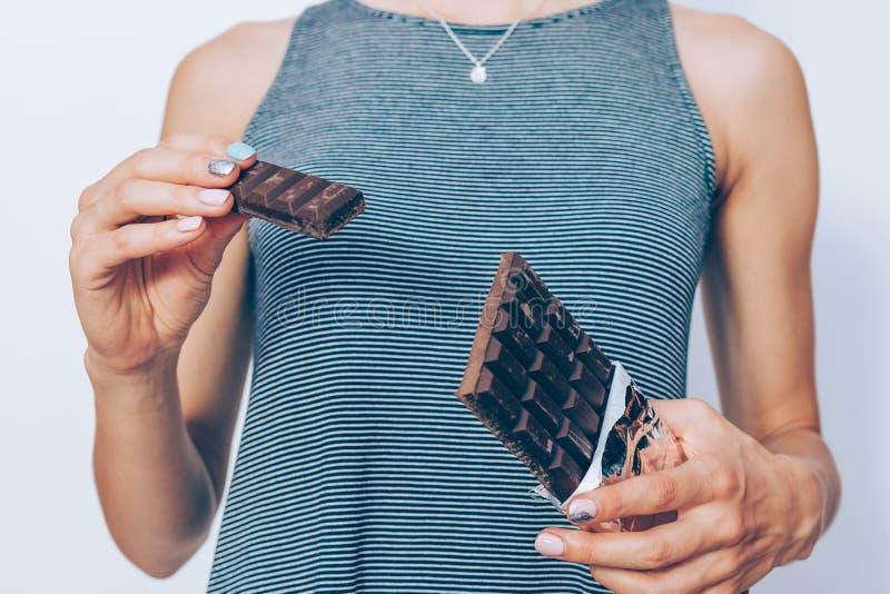 Les mains de la femme tenant la barre de chocolat foncée image libre de droits