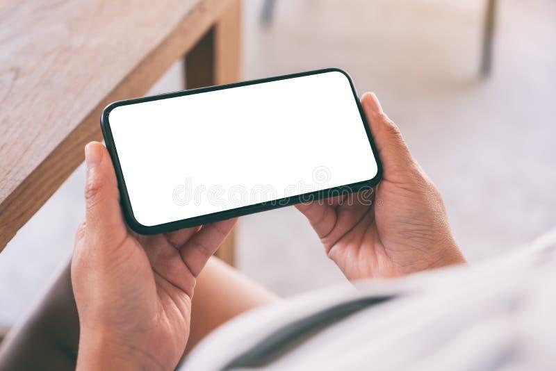 Les mains de la femme tenant le t?l?phone portable noir avec l'?cran blanc vide horizontalement en caf? photos stock