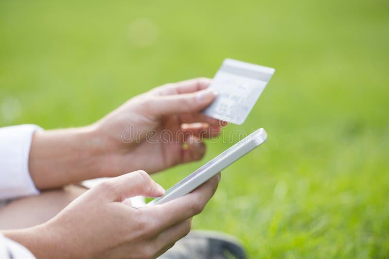 les mains de la femme tenant une carte de crédit et à l'aide du téléphone portable image libre de droits