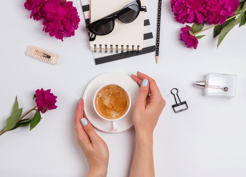 Les mains de la femme tenant une tasse de café sur la table avec les accessoires et les pivoines féminins photo libre de droits