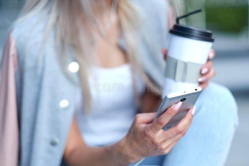Les mains de la femme utilisant le téléphone et tenir la tasse de papier avec du café Concept en ligne d'Internet de hippie de l' photo stock