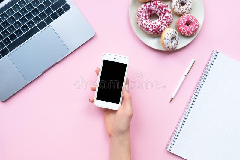 Les mains de la femme de vue tenant le smartphone blanc avec le copyspace noir sur le fond rose avec d'autres accessoires Affaire photographie stock libre de droits