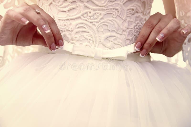 Les mains de la fille de jeune mariée tiennent l'arc blanc sur la robe de mariage image libre de droits