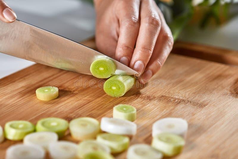 Les mains de la fille ont coupé le poireau organique en morceaux sur un conseil en bois Nourriture saine images libres de droits