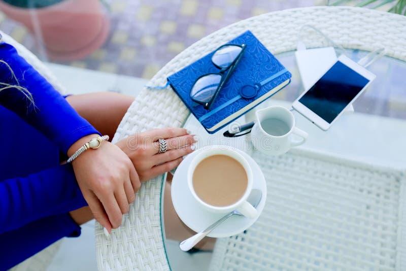 Les mains de la fille sur une table près d'une tasse de café et d'un bloc-notes images stock