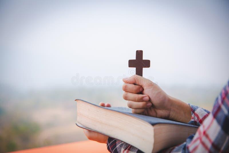 Les mains de la jeune femme de prière avec la croix et la Sainte Bible en bois Concept de religion photos stock