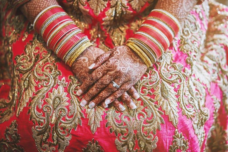 Les mains de la jeune mariée indienne avec le tatouage de henné de menhdi et du groupe de bracelets de scintillement sur son poig photographie stock