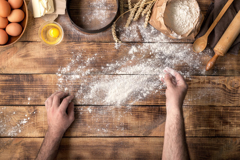 Les mains de mâles arrosent avec la table en bois de farine pour faire la pâte images libres de droits