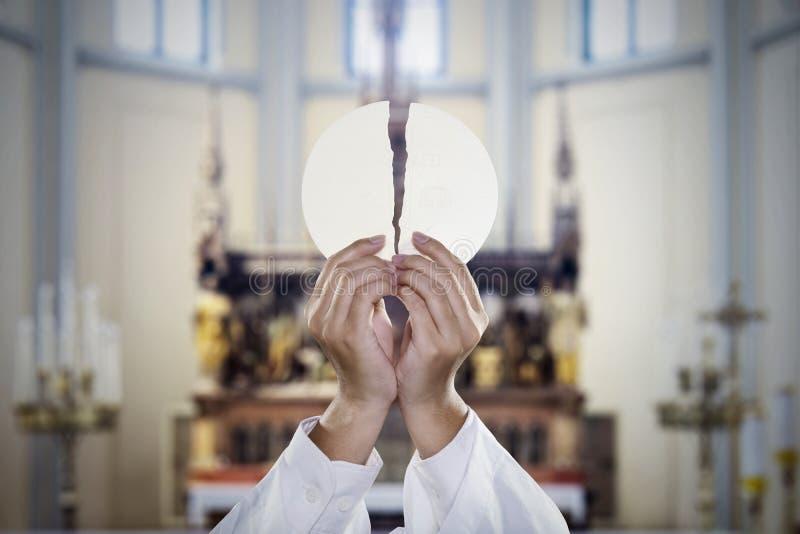 Les mains de pasteur ont dédoublé un pain de communion dans l'église photos libres de droits