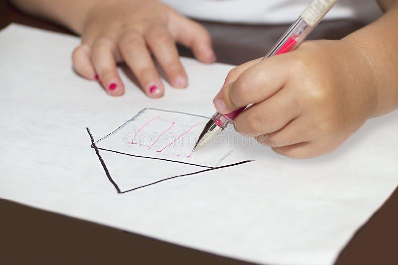 Les mains de petite fille avec ballpen dessinant une maison photo libre de droits