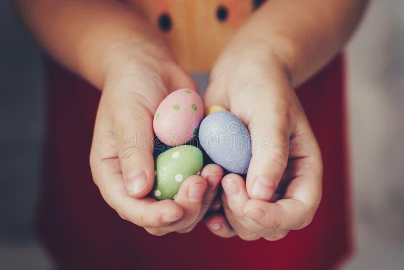 Les mains de petite fille tenant des oeufs de pâques ont peint la couleur en main photos stock