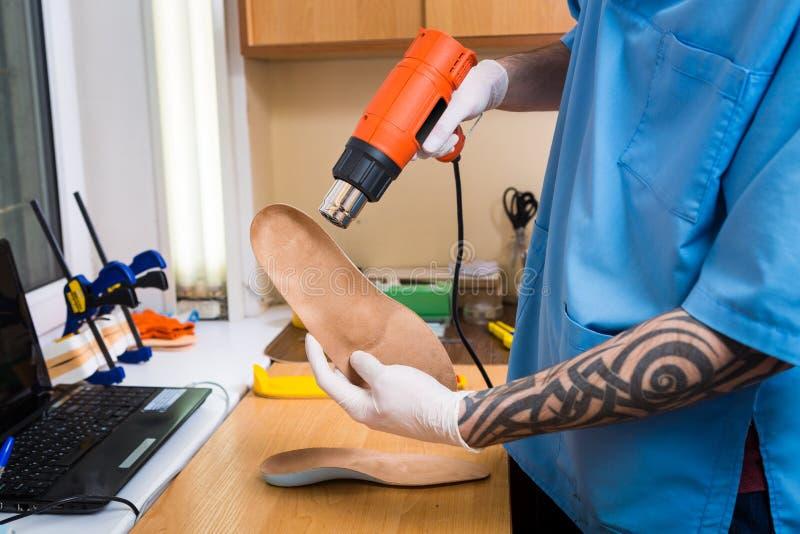Les mains de plan rapproché du jeune homme avec le tatouage dans l'atelier habillé dans l'uniforme bleu font différentes semelles photos stock