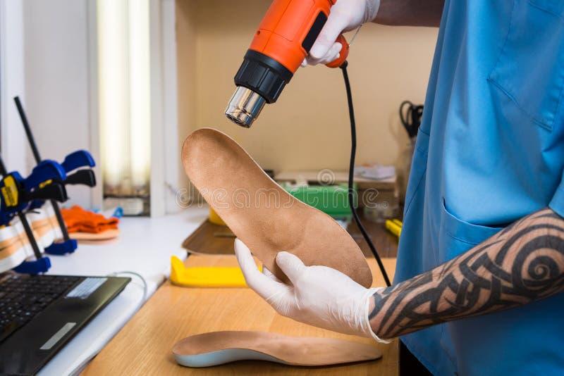 Les mains de plan rapproché du jeune homme avec le tatouage dans l'atelier habillé dans l'uniforme bleu font différentes semelles images stock