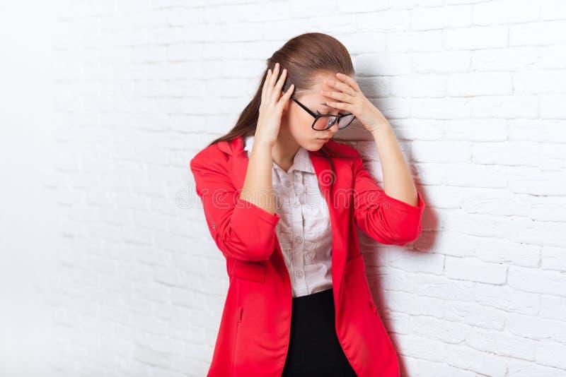 Les mains de prise de femme d'affaires sur la tête, mal, font souffrir les verres rouges de veste d'usage déprimé soumis à une co images libres de droits