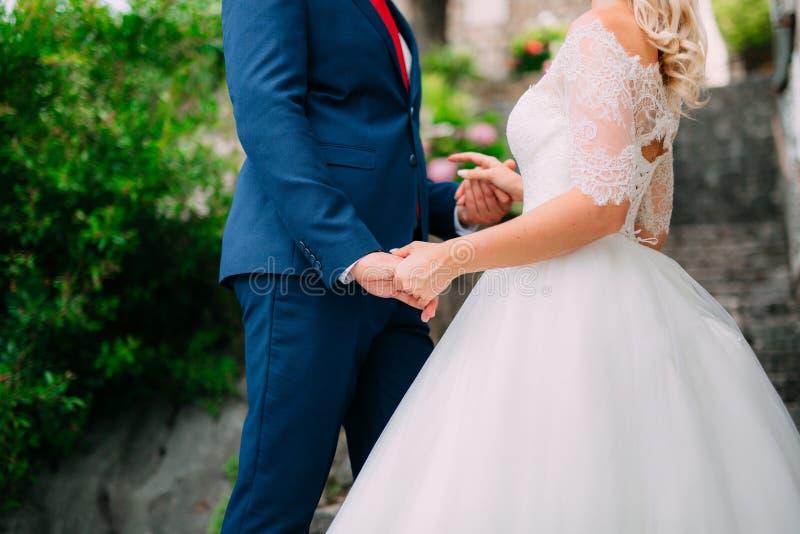 Les mains de prise de nouveaux mariés Accouplez les mains de fixation Épouser en Monte image stock