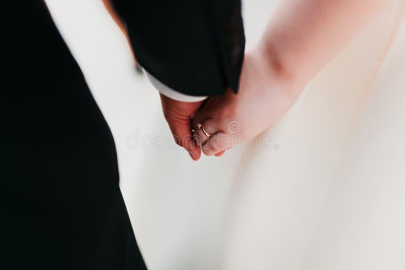 Les mains de prise de nouveaux mariés images libres de droits