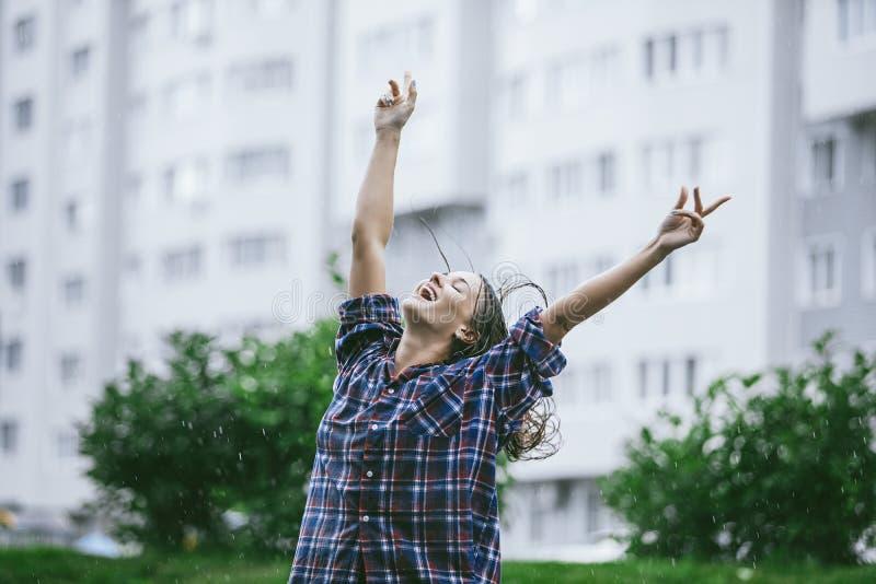 Les mains de sourire heureuses de bonheur de femme ont tendu vers la pluie images stock