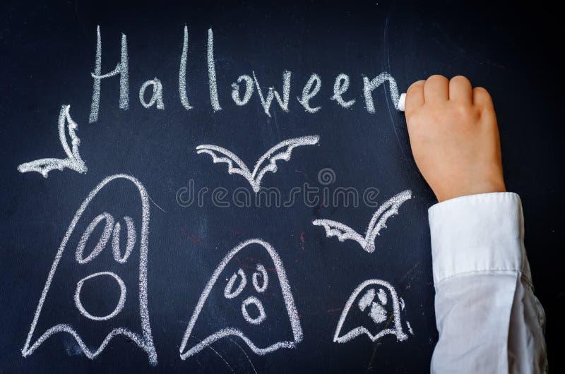 Les mains des enfants écrivant sur un tableau noir photo libre de droits