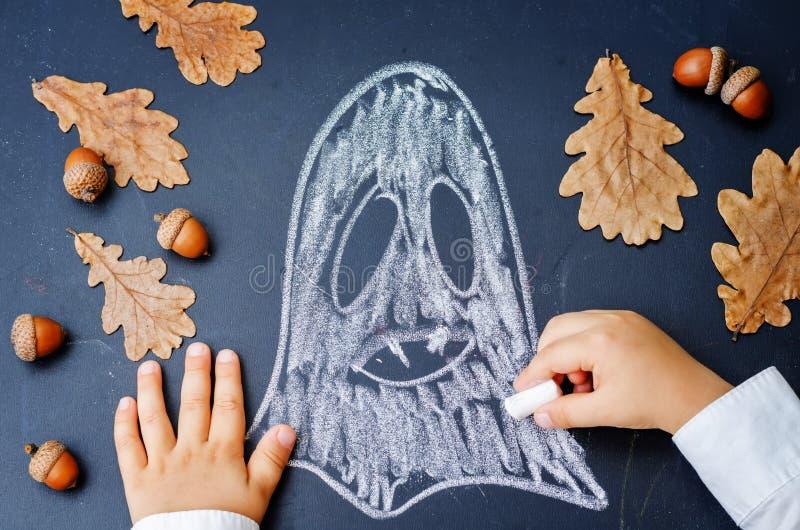 Les mains des enfants écrivant sur un tableau noir image libre de droits