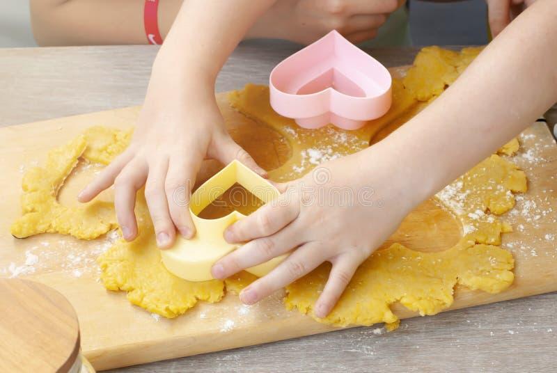 Les mains des enfants avec une forme pour des biscuits Ustensiles de cuisine à l'arrière-plan, formes pour des biscuits, goupille photographie stock