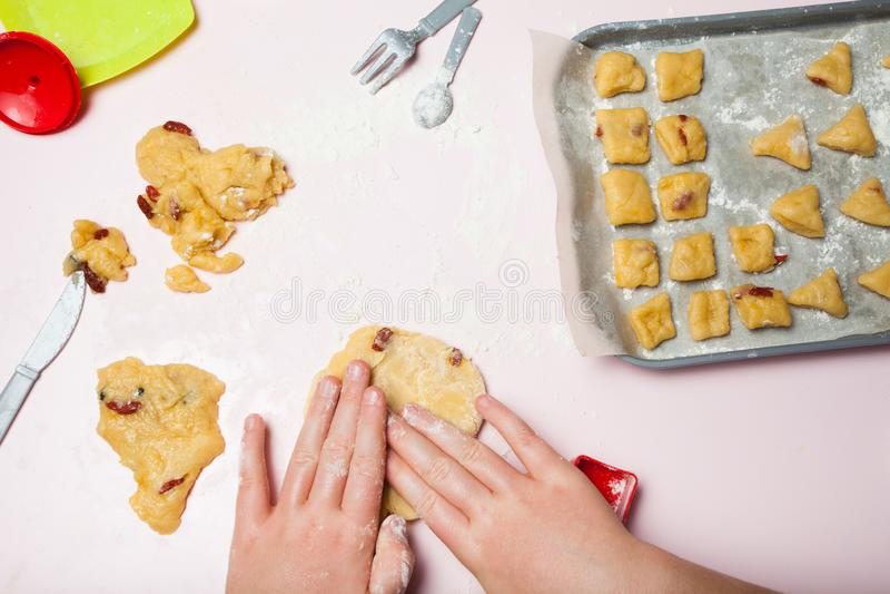 Les mains des enfants préparent les biscuits délicieux avec des baies, la vue supérieure Plats de jouet, le concept des gâteaux f photo stock