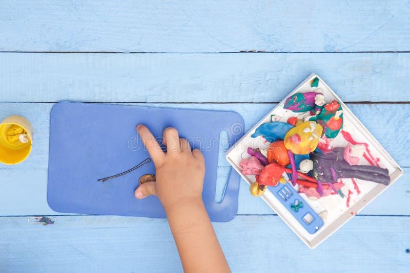 Les mains des enfants sculptent des figures d'argile sur une table bleue La vue ? partir du dessus photos stock