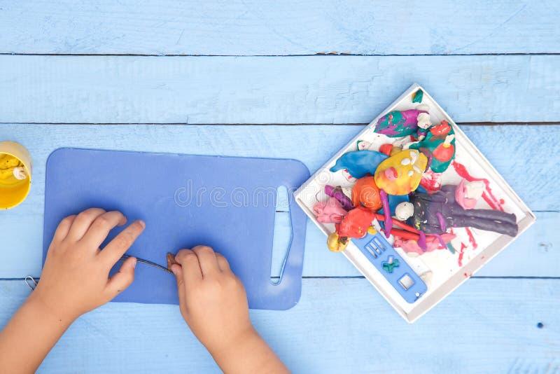 Les mains des enfants sculptent des figures d'argile sur une table bleue La vue ? partir du dessus photographie stock libre de droits