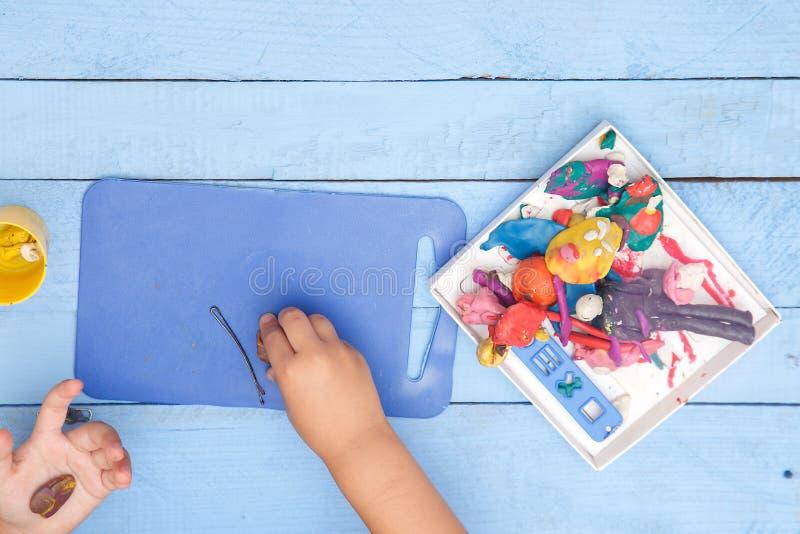 Les mains des enfants sculptent des figures d'argile sur une table bleue La vue ? partir du dessus image stock