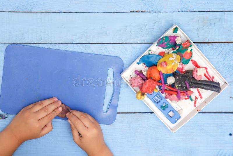 Les mains des enfants sculptent des figures d'argile sur une table bleue La vue ? partir du dessus photos libres de droits