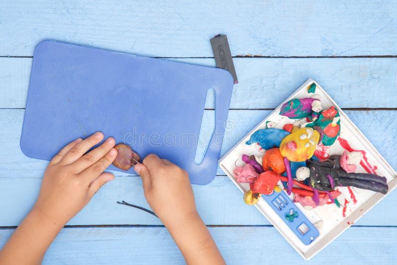 Les mains des enfants sculptent des figures d'argile sur une table bleue La vue ? partir du dessus photo stock